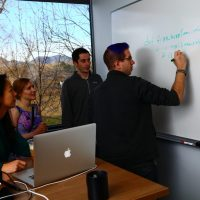 Uber Team Writing on Whiteboard Photo