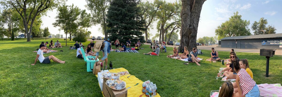 Employees at stream gather at a company picnic.